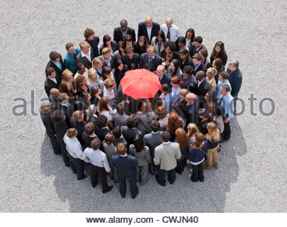 Umbrella at center of circle formed by business people - Stock Photo