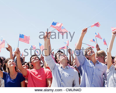 Smiling people waving American flags and looking up in crowd - Stock Photo