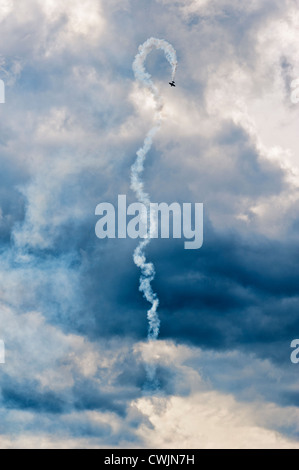 Single plane performing aerial aerobatics with a smoke trail against a moody sky backdrop. - Stock Photo