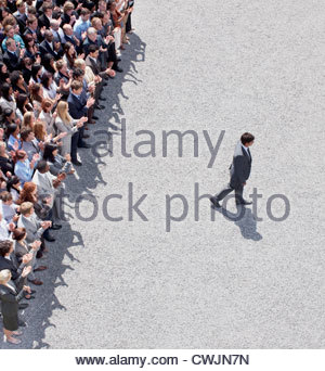 Businessman walking away from clapping crowd - Stock Photo