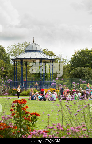 Family's enjoying the sunshine around the bandstand at the War Memorial Park at Romsey - Stock Photo