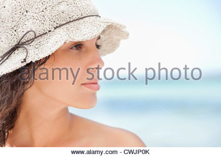 Close up of serious woman in sun hat on beach - Stock Photo