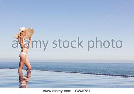 Woman in bikini and sun hat standing in infinity pool - Stock Photo