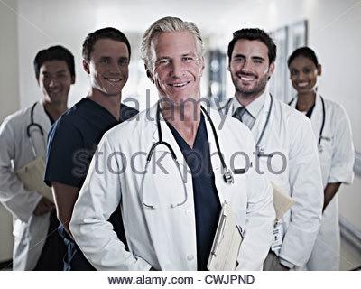 Portrait of smiling doctors and nurse in hospital corridor - Stock Photo