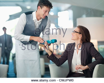Waiter processing businesswoman's credit card with credit card reader - Stock Photo