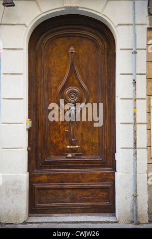 Huge wooden front door with hand style knocker of apartment building in Barcelona, Catalonia, Spain, ES - Stock Photo