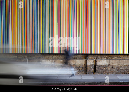 Bright vertical stripes with blurred figure passing by - Stock Photo