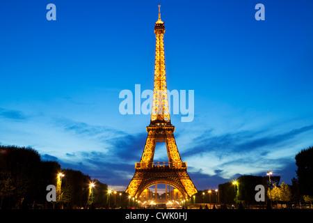 Paris Eiffel tower illuminated at night from the Champs de Mars gardens France EU Europe - Stock Photo