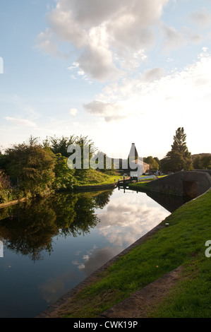 Calm summer evening with trees reflected in a canal basin with locks and the historic Red House Glass Cone, in the - Stock Photo