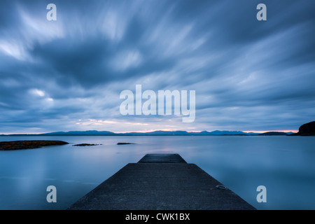 Scenic coastal view over to the Isle of Mull from Oban, Scotland with centrally placed jetty and clouds streaking - Stock Photo