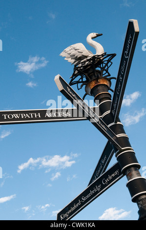 Victorian-style  black canal signpost pointing to a towpath in Dudley with a swan on the top of it against a bright blue sky