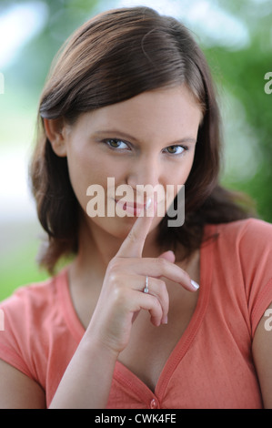 Young woman holding a finger on the lips - Stock Photo