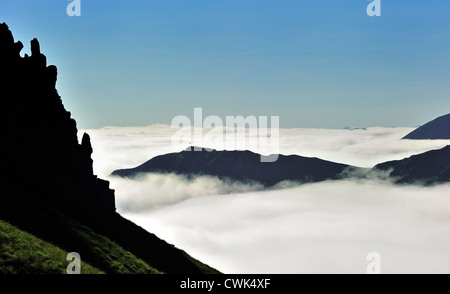 View over silhouetted jagged mountain edge and mountains covered in mist at sunrise near the Col du Tourmalet, Pyrenees, - Stock Photo
