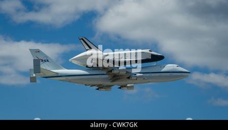 Space shuttle Enterprise mounted atop a NASA 747 Shuttle Carrier Aircraft flies over John F. Kennedy Airport April - Stock Photo