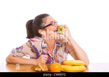 Happy woman eating big apple, with fruits and cakes on table. - Stock Photo