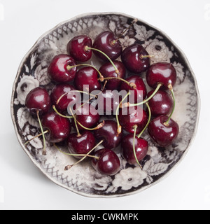 some cherries on an antique plate - Stock Photo