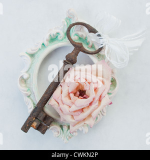 antique, rusty key on an old, vintage frame with dry roses