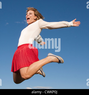 happily jumping woman on a bright blue sky - Stock Photo