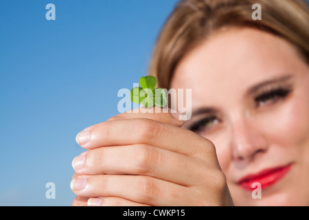 woman with four leafed clover - Stock Photo