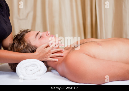 man getting neck face and head massage at spa - Stock Photo