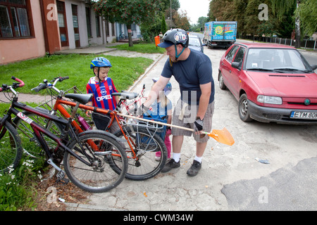 Polish dad loading newly purchased broom on his bike for a ride home with his children. Rzeczyca Central Poland - Stock Photo