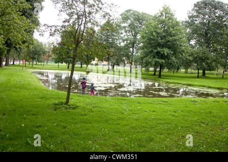 Polish children playing by city pond.  Paderewski Park Rzeczyca Central Poland - Stock Photo