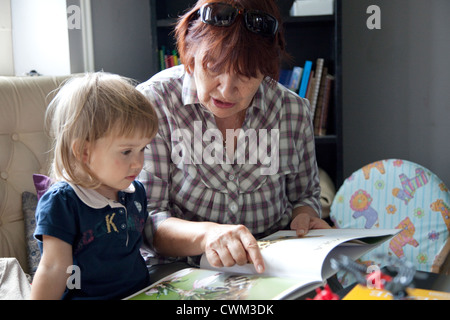 Polish grandma (babcia) reading to her young granddaughter age 63 and 2. Zawady Central Poland - Stock Photo