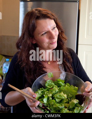 Pleased Polish woman age 32 holding a glass salad bowel of fresh greens in her kitchen. Zawady Central Poland - Stock Photo