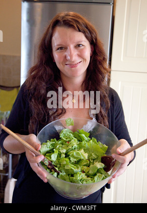 Happy Polish woman age 32 holding a glass salad bowel of fresh greens in her kitchen. Zawady Central Poland - Stock Photo