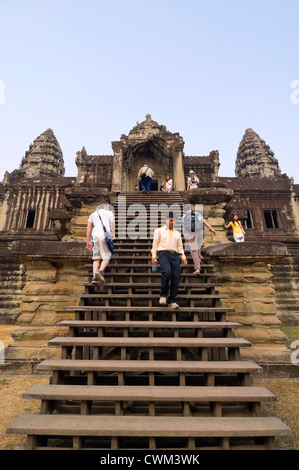 Vertical view of tourists climbing the steep steps inside Angkor Wat - Stock Photo