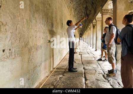 Horizontal view of a guide and a group of tourists standing infront the amazing carvings at Prasat Angkor Wat - Stock Photo