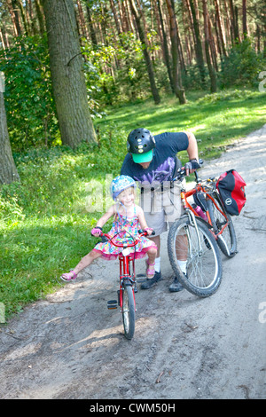 Dad giving a start to balancing daughter on bicycle Polish National Forest logging trail age 4 and 37. Zawady Central - Stock Photo