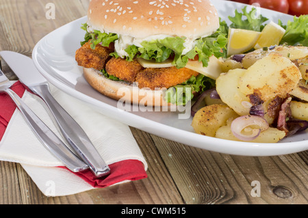 Fried Potatoes with Fish Burger on wooden background - Stock Photo
