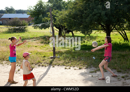 Teens and children playing volleyball in village sandlot course. Mala Wola Central Poland - Stock Photo