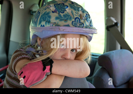 Young girl age 4 wearing helmet and pink fingerless gloves resting in car after a long bicycle ride. Zawady Central - Stock Photo