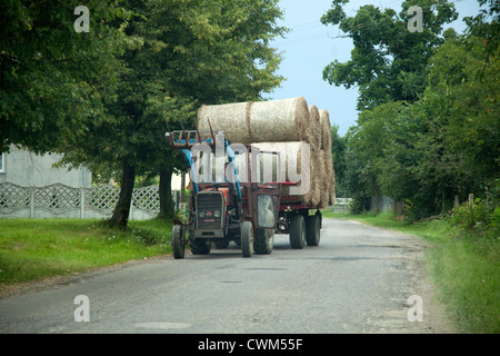 Cart full of farmers hay bails transported down village lane. Zawady Central Poland - Stock Photo