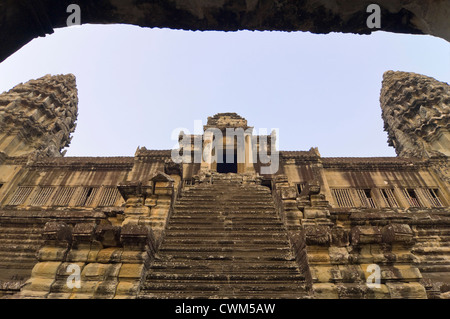 Horizontal view of tourists climbing the steep steps inside Angkor Wat - Stock Photo