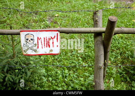 Land mine skull and crossbones warning sign in Polish on barbed wire fence protecting Hitler's Bunker. Konewka Central - Stock Photo