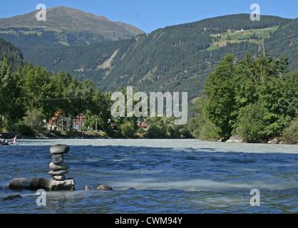 Rocks stacked on the shore of River Inn, next to Aktiv Camping, Prutz, Austria - Stock Photo