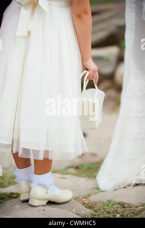 Lower section of young flower girl in pretty dress carrying a purse at an outdoor wedding. - Stock Photo