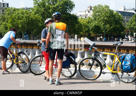Paris, France - July  2012 -  Cyclists having a break on a bridge. - Stock Photo
