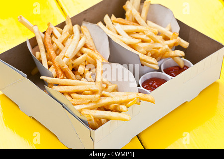 Portions of french fried potatoes with ketchup in cardboard take-out box - Stock Photo