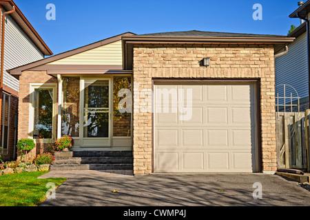 Suburban small bungalow house with single garage - Stock Photo