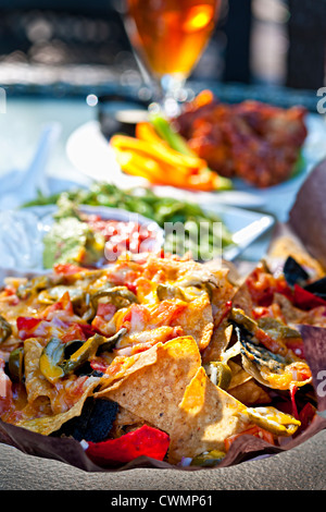 Basket of nachos and other appetizers on restaurant table - Stock Photo