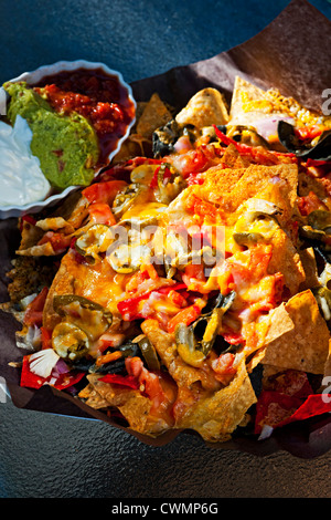 Basket of nachos with cheese jalapeno and toppings - Stock Photo