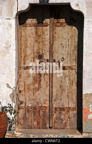 Weathered wooden door of an old stone house on Pelion Peninsular, Thessaly, Greece - Stock Photo