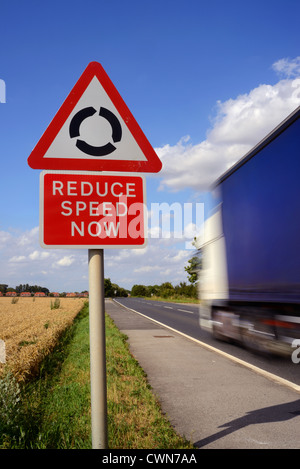lorry passing reduce speed now warning sign and roundabout ahead uk - Stock Photo