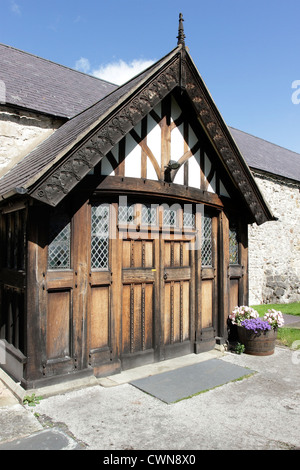 The ornate carved wooden porch at the entrance of St Michael's Parish Church, Abergele, North Wales. - Stock Photo