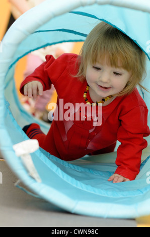 Little girl crawling through tunnel - Stock Photo