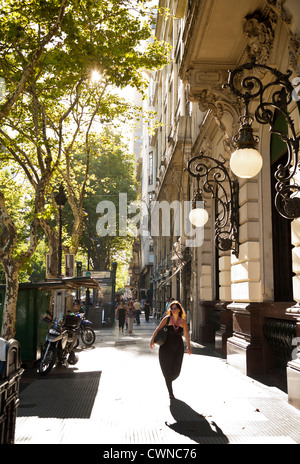 Woman walks on Avenida de Mayo, Buenos Aires, Argentina. - Stock Photo